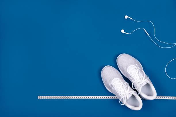 Weiße Sneakers mit Maßband und Kopfhörern (Kopfhörer)   auf blauem Hintergrund. – Foto