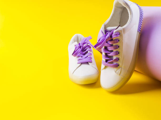 White sneakers with purple laces on yellow background stock photo