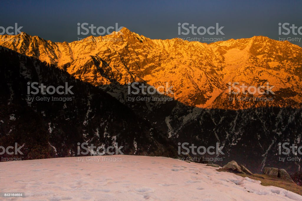 White snow mountains turned golden due to suns rays at golden hour or sunset at Triund, Mcleod ganj, Dharamsala, himachal pradesh, India. Mind blowing scene. golden mountains, hills, camping, dusk stock photo
