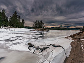 Panoramic view of the snow white frozen lake and a pine woodland nearby.