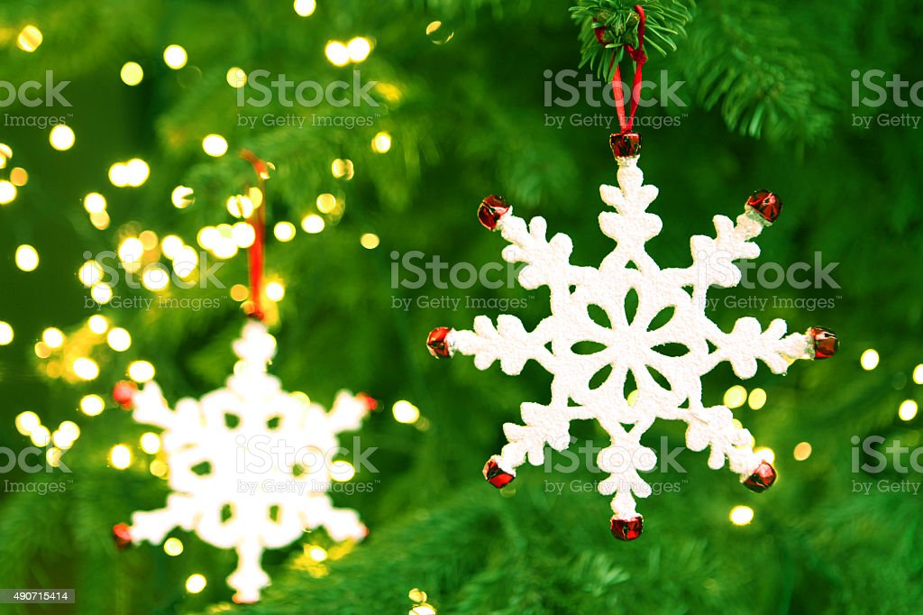 White Snowflake Ornament Hanging on a Lit Christmas Tree stock photo