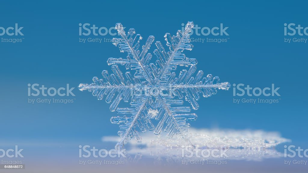 White snowflake sparkle on bight blue background - horizontal version stock photo