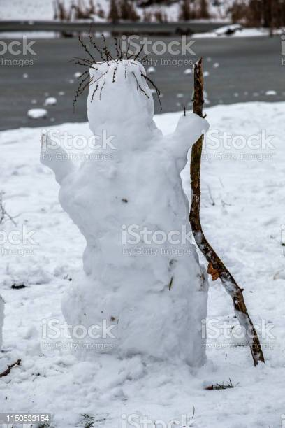 Photo of White snowman mit a wooden stick and hair made of dry grass