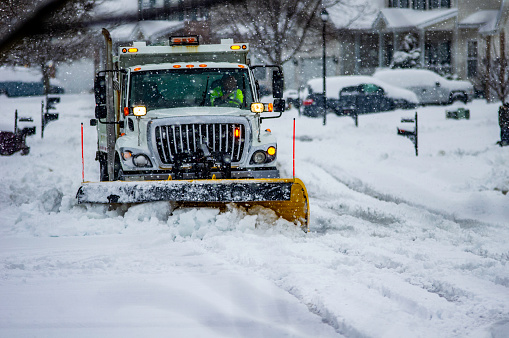 White snowplow service truck with orange lights and yellow plow blade clearing residential roads of snow while flakes are still falling