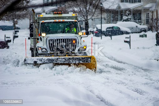 Heavy equipment driver working to push snow to the side of the streets after a blizzard