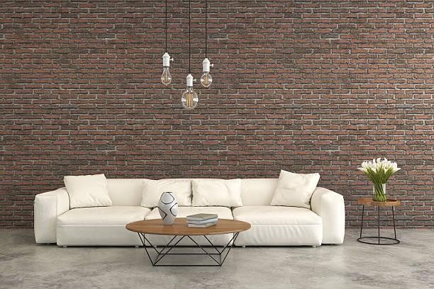 white sofa in front of a brick wall - betonboden wohnzimmer stock-fotos und bilder