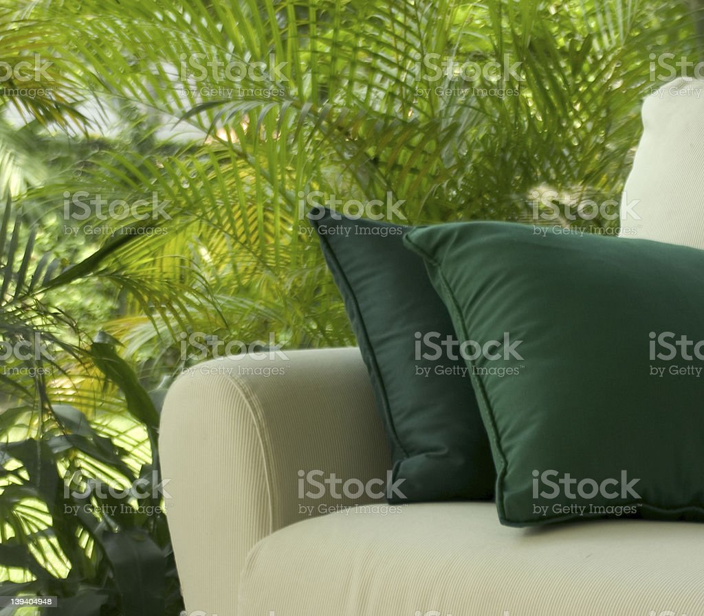 White sofa with green pillows on it placed outdoors stock photo