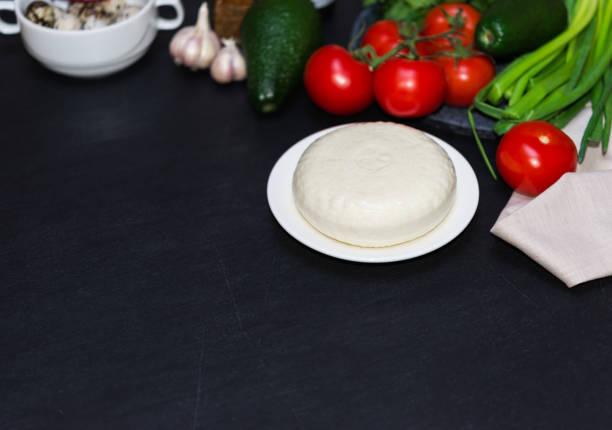 Weißer Weichkäse. Milchnahrung und Tomaten auf dunklem Hintergrund. Gesunde seradienende Nahrung. – Foto