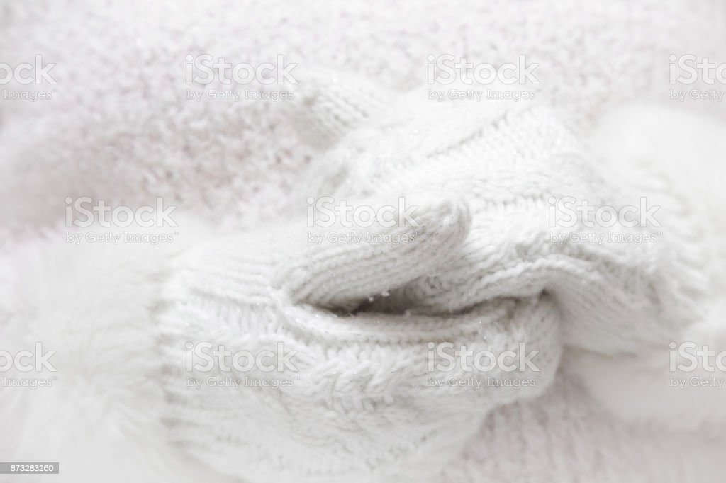 White, soft knitted womanly mittens on fluffy sweater background. Winter time wear concept. stock photo
