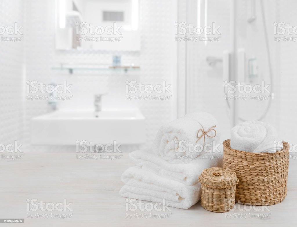 White spa towels and wicker baskets on defocused bathroom interior stock photo