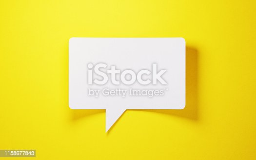 White speech bubble shaped post it note on yellow background.  Horizontal composition with copy space.