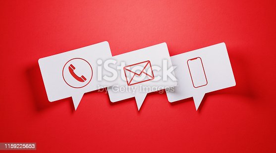 White speech bubble shaped post it notes with communication symbols on red background.  Horizontal composition with copy space.