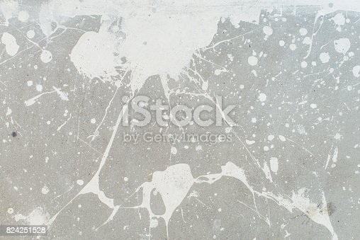 istock White splash on gray background concrete wall, messy, splotchy, surface. Decorative wet paint drops, abstract art. 824251528