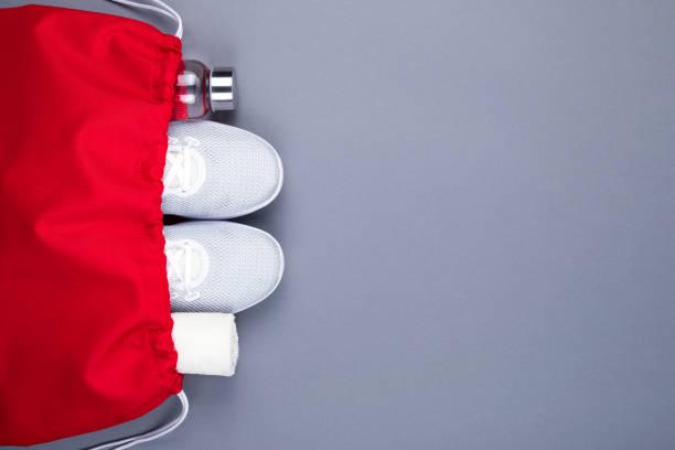 Weiße Sportschuhe Turnschuhe, Glas wasserflasche und Handtuch in roter Sporttasche auf grauem Hintergrund. – Foto