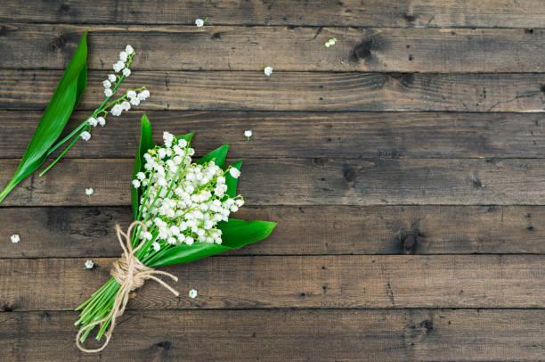 Weiß Frühlingsblumen. Bouquet von Lily Of The Valley auf einem dunklen Braun-Holz-Hintergrund. Gruß für Frauen, Muttertag, Geburtstag feiern. Textfreiraum – Foto