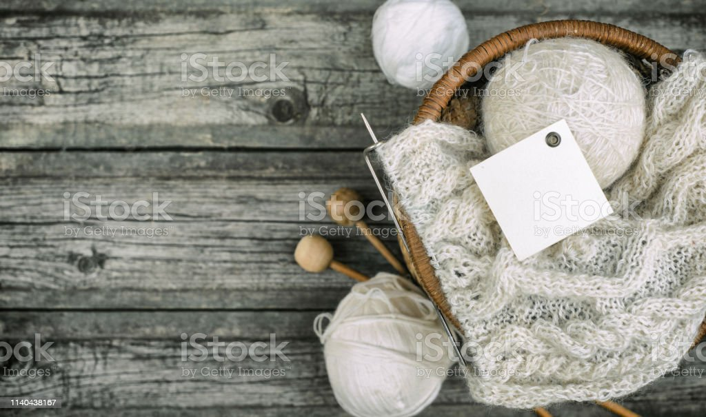 White square label on wool threads roll to basket with knitting and...