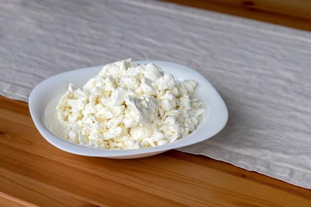 Une plaque carrée blanche remplie de fromage cottage se dresse sur une nappe en lin sur une table en bois. Mise au point sélective - Photo