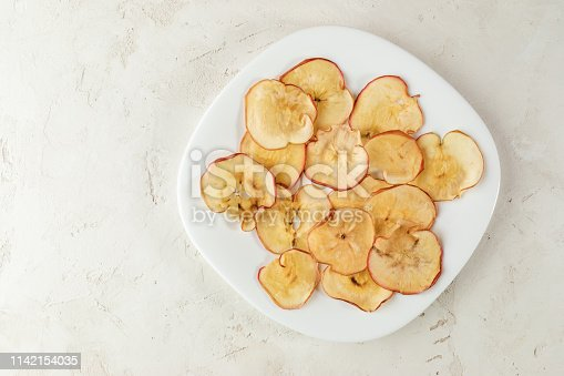 White square plate with apple chips on textured white background. Healthy snack. Top view, copy space.