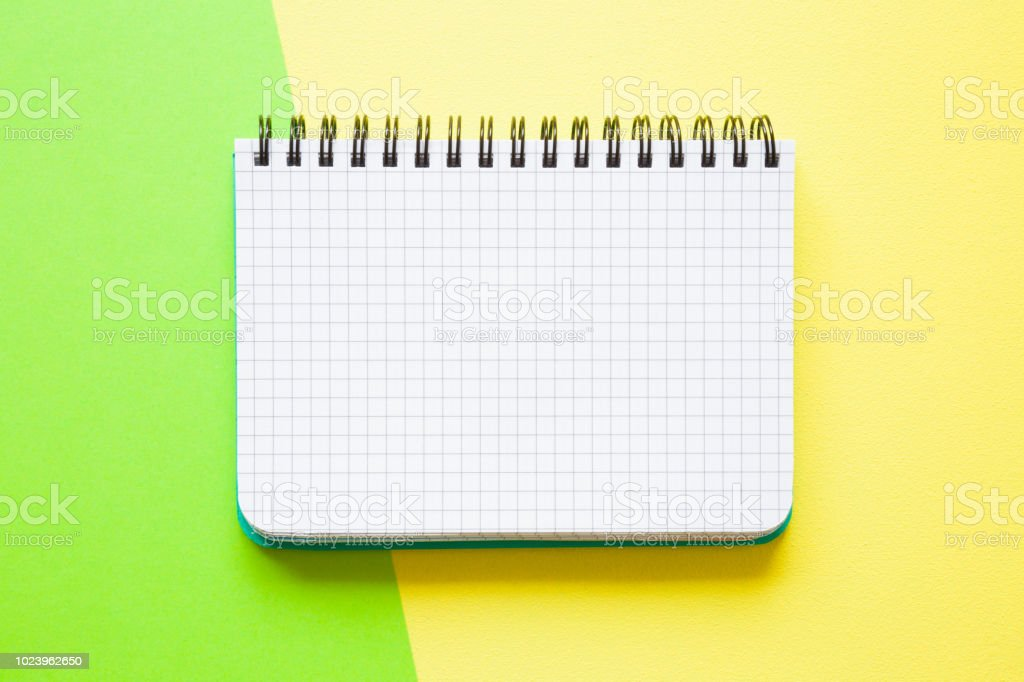 White squared notebook on the green, yellow work table. Empty place for daily plans, important information, ideas, memories or other text on the grid paper. Bright colors. Top view. Flat lay. stock photo