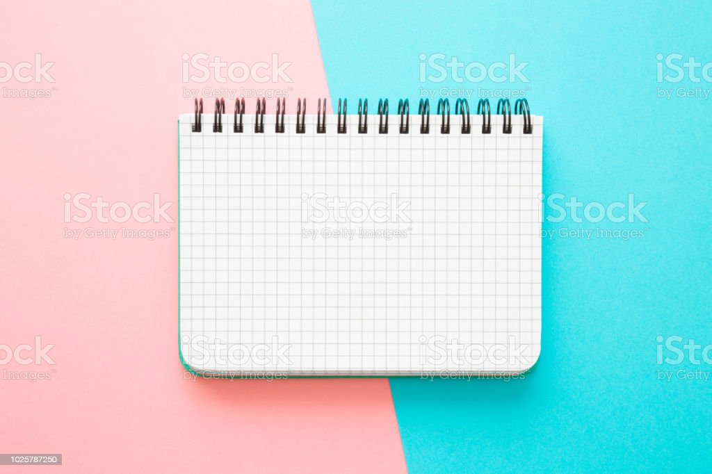 White squared notebook on the pink, turquoise blue work table. Empty place for daily plans, important information, ideas, memories or other text on the grid paper. Pastel tone colors. Top view. stock photo