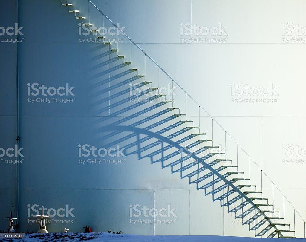 White Staircase and Shadow on Oil Storage Tank stock photo