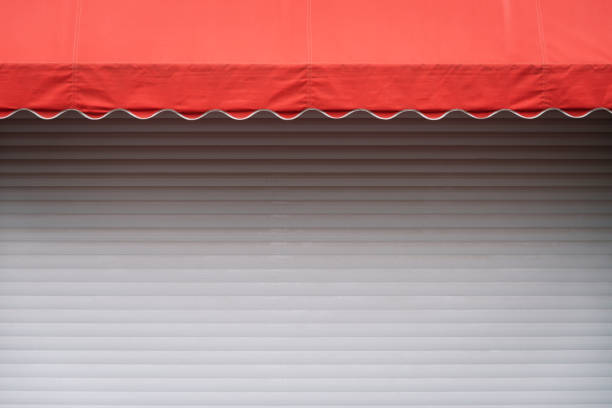 White stall with red sunshade White stall with closed shutters and red sunshade. Geometric contrast background with copy space for text and design canopy stock pictures, royalty-free photos & images