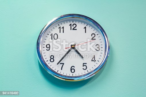 white steel clock on green pastel concrete wall background in living room