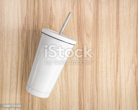 1129148925istockphoto White steel mug with tube on wood background. Insulated container for keep your drink. 1038723120
