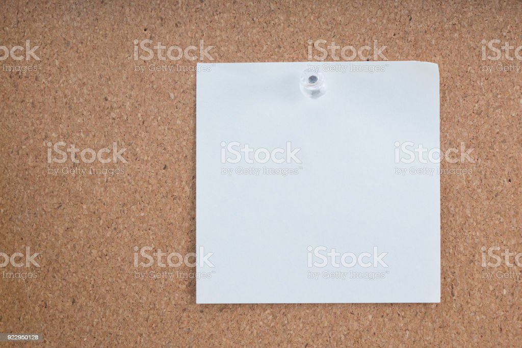 white sticky note or post is on cork bulletin billboard. stock photo
