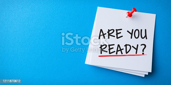 White Sticky Note With Are You Ready And Red Push Pin On Blue Background