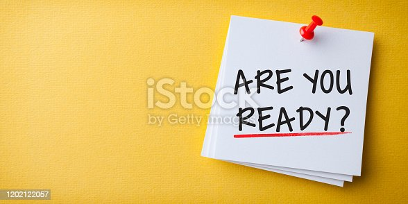 White Sticky Note With Are You Ready? And Red Push Pin On Cork Board