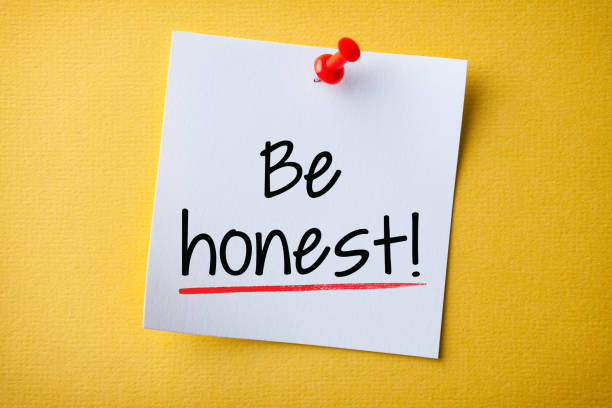 White Sticky Note With Be Honest And Red Push Pin On Yellow Background stock photo