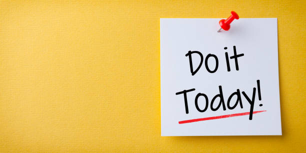 White Sticky Note With Do it Today And Red Push Pin On Yellow Background stock photo