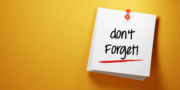 white sticky note with don't forget message and red push pin on yellow background - reminder stock photos and pictures