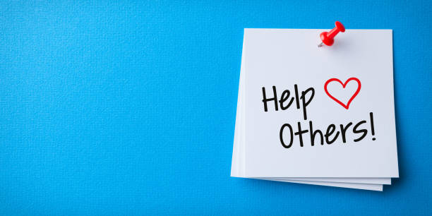 White Sticky Note With Help Others And Red Push Pin On Blue Background stock photo