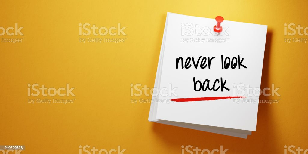 White Sticky Note with Never Look Back Message And Red Push Pin On Yellow Background stock photo