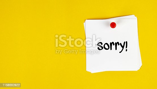 White Sticky Note With Sorry Message And Red Push Pin On Yellow Background