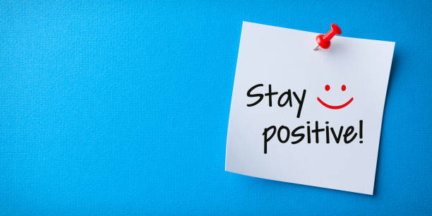 White Sticky Note With Stay Positive And Red Push Pin On Blue Background stock photo