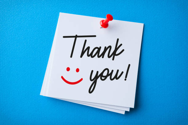 White Sticky Note With Thank You And Red Push Pin On Blue Background stock photo