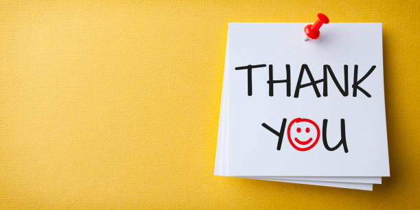 White Sticky Note With Thank You And Red Push Pin On Yellow Background stock photo