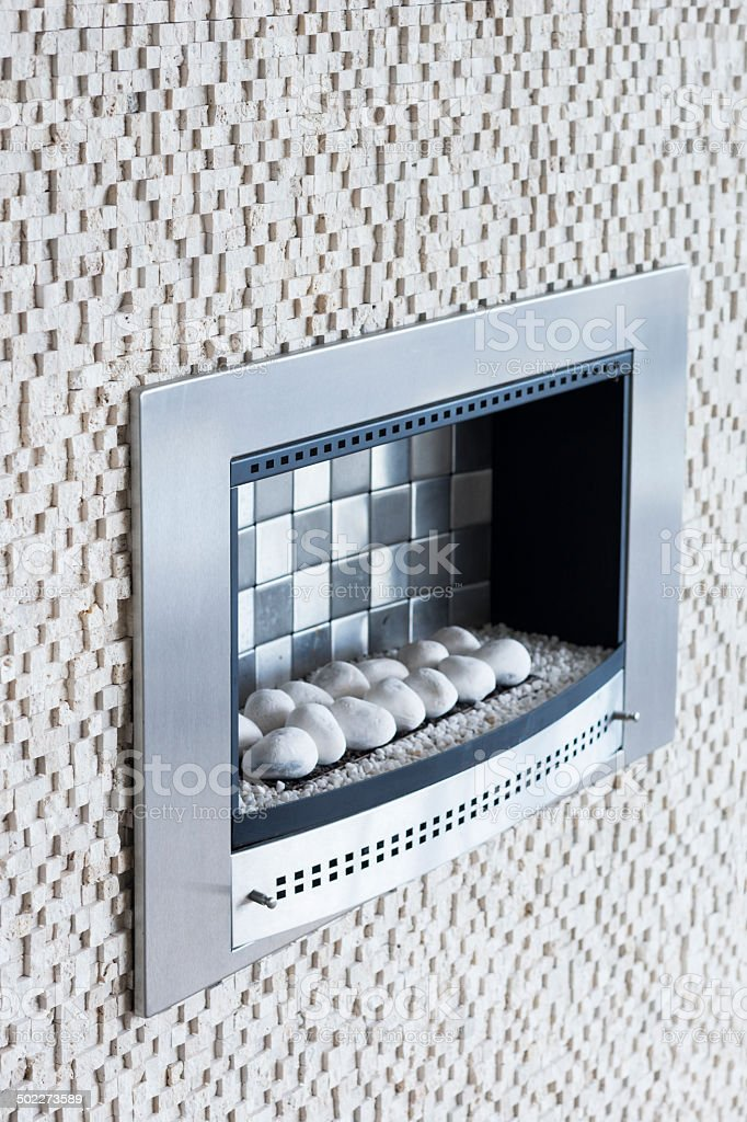 White stone contempory gas fireplace stock photo