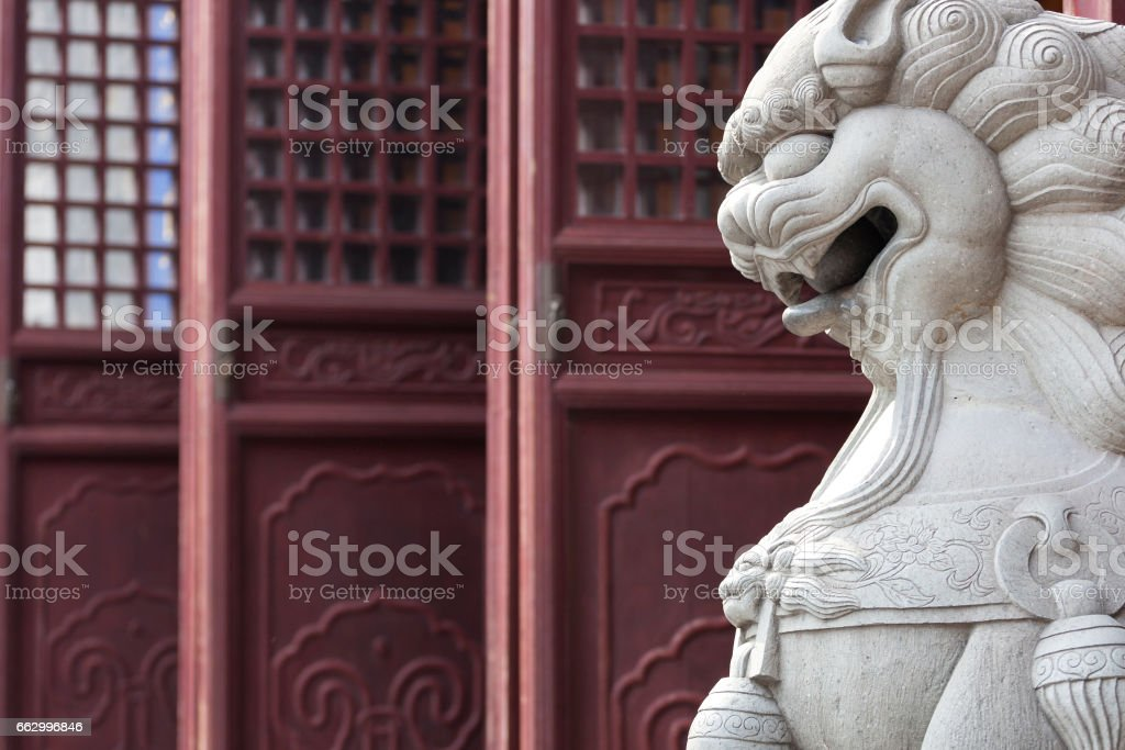 White stone Lion statue in front of chinese temple stock photo