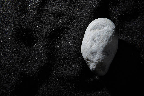 white stone on black beach Stone on a black beach. in the morning. The scene is a  reconstruction made in studio. black sand stock pictures, royalty-free photos & images
