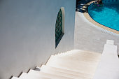 white stone stairs, ladder outside on sunny day. white house with swimming pool. Holiday concept.