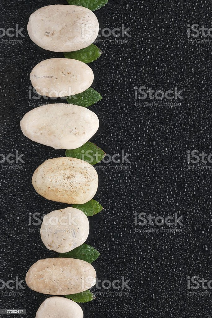 White stones and leaf  lie on a wet black background royalty-free stock photo
