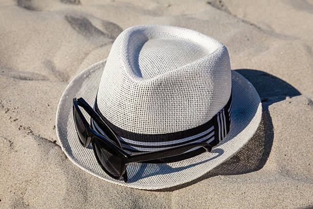 White Straw Fedora with Sunglasses on Beach stock photo