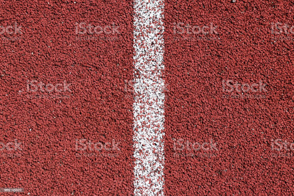White strip of markings on a red background of rubberized cover of sports grounds and stadiums for outdoor use. Red and white relief texture of the background. zbiór zdjęć royalty-free