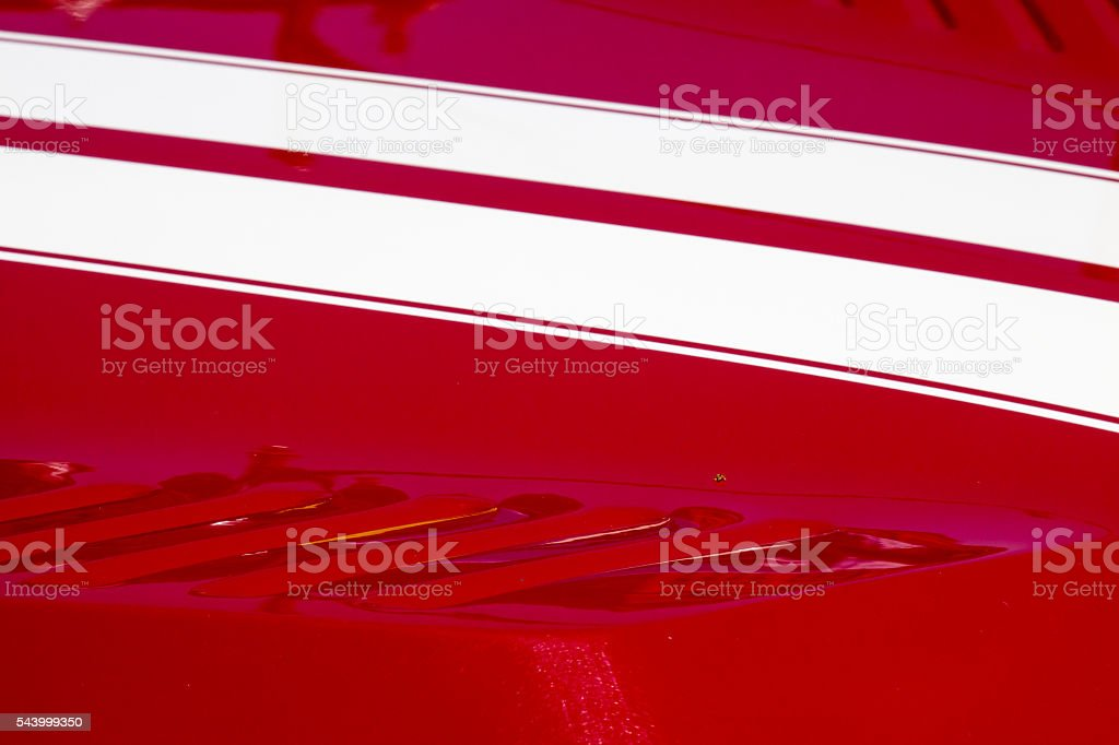 White stripes on the red hood of a muscle car stock photo