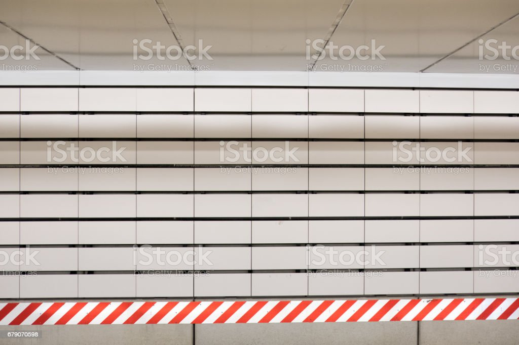 White subway tile and red and white striped caution sign or tape in a...