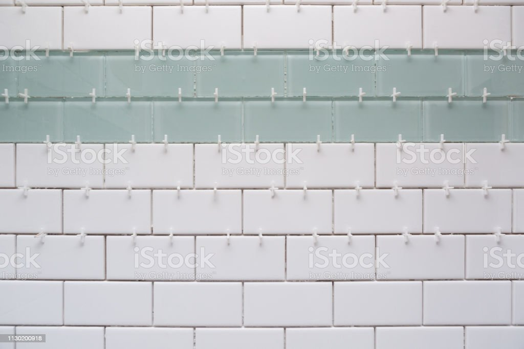 White subway tile, green accent tile with spacers without grout stock photo